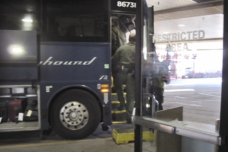 In this Thursday, Feb. 13, 2020 photo, agents for Customs and Border Protection board a Greyhound bus headed for Portland, Ore., at the Spokane Intermodal Center, a terminal for buses and Amtrak, in Spokane, Wash. A Customs and Border Protection memo obtained by The Associated Press confirms that bus companies such as Greyhound do not have to allow Border Patrol agents on board to conduct routine checks for illegal immigrants, contrary to Greyhound's long insistence that it has no choice but to let the agents on board. (AP Photo/Nicholas K. Geranios)