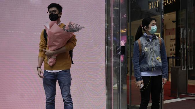 Seorang pria dan wanita mengenakan masker menunggu di sudut jalan pada Hari Valentine di Hong Kong, Jumat, (14/2/2020). Hari Valentine pada tanggal 14 Februari adalah sebuah hari di mana para kekasih dan mereka yang sedang jatuh cinta menyatakan cintanya. (AP Photo/Kin Cheung)