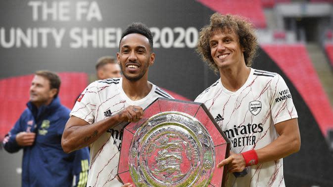 Penyerang Arsenal, Pierre-Emerick Aubameyang dan bek David Luiz berpose dengan trofi Community Shield usai pertandingan melawan Liverpool di stadion Wembley, London, Sabtu, (29/8/2020). Arsenal mengalahkan Liverpool 5-4 dalam adu penalti setelah pertandingan seri 1-1. (Justin Tallis/Pool via AP)