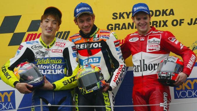 Pebalap Suzuki, Akira Ryo (kiri), berpose bersama rider Honda, Valentino Rossi (tengah), dan Carlos Checa (Ducati) di podium MotoGP Jepang di Sirkuit Suzuka pada 2002. (MotoGP)
