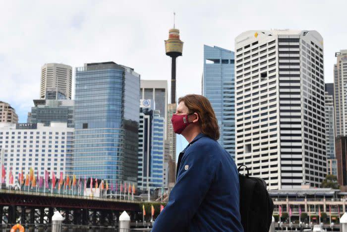 A person walks past a Sydney skyline