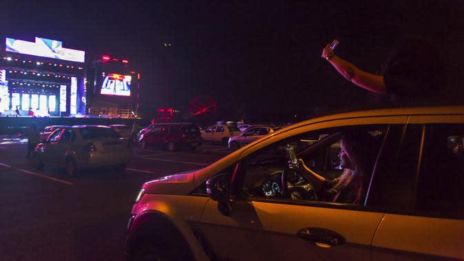 Pengunjung menonton pertunjukan dari dalam mobil mereka di taman hiburan horor Hopi Hari, pinggiran Vinhedo, Sao Paulo, Brasil, Jumat (4/9/2020). Karena pembatasan akibat COVID-19, taman hiburan horor Hopi Hari menampilkan pertunjukan secara drive-thru. (AP Photo/Carla Carniel)