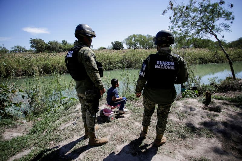 "FILE PHOTO: A migrant boy, an asylum seeker sent back to Mexico from the U.S. under the ""Remain in Mexico"" program officially named Migrant Protection Protocols (MPP), is seen near two members of the Mexican National Guard at a provisional campsite near th"