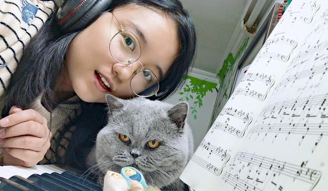 Piano teacher Mary Zhu with one of her pet cats. Photo: Handout