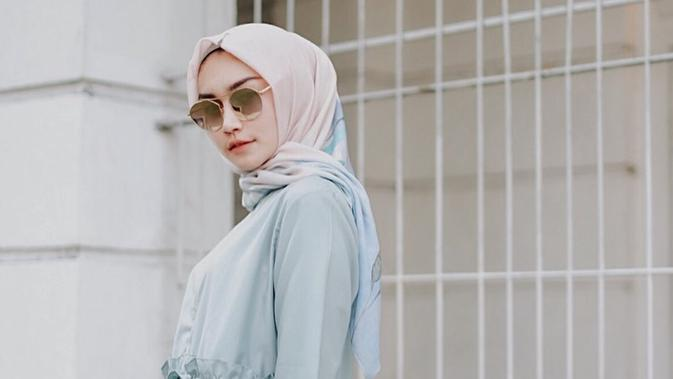 Tampil dengan blouse tosca dan hijab motif, gaya pemeran sinetron Dia Bukan Cinderella ini semakin elegan dengan kacamata berlensa gelap. Penampilannya terlihat santai namun berkelas. (Liputan6.com/IG/@melodyprima)