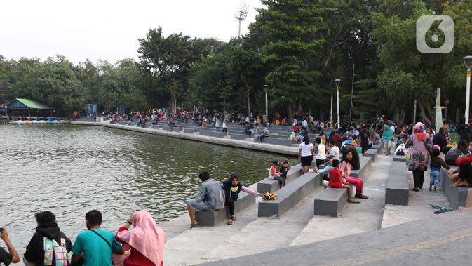 Warga duduk menikmati suasana Danau Sunter, Jakarta, Sabtu (27/6/2020). Beragam aktivitas dilakukan warga sambil menikmati waktu sore di area Danau Sunter, Jakarta. (Liputan6.com/Helmi Fithriansyah)