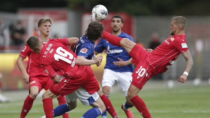 Pemain Union Berlin, Robert Andrich, berebut bola dengan pemain Schalke pada laga Bundesliga di Weserstadion Minggu (7/6/2020). Kedua tim bermain imbang 1-1. (AP/Michael Sohn)
