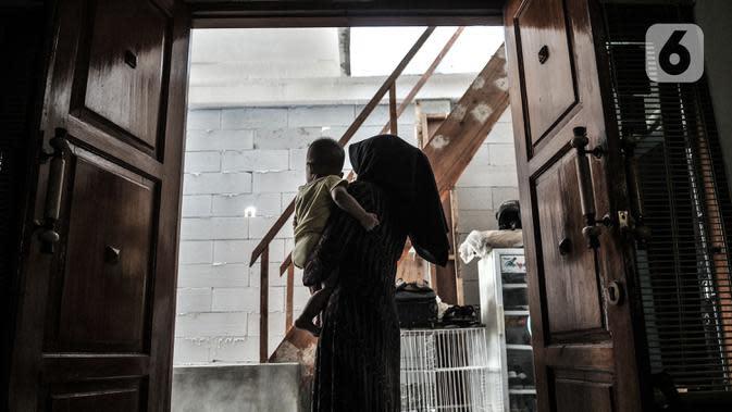 Wiwiek menggendong cucunya di depan rumahnya yang tertutup tembok bangunan sekolah di Jalan Cempaka Baru I, RT 015/003, Kemayoran, Jakarta, Senin (31/8/2020). Pembangunan itu menutup akses jalur keluar masuk dan harus melewati pintu samping. (merdeka.com/Iqbal S Nugroho)