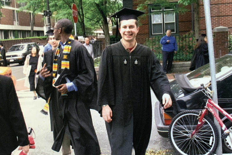 In this image provided by the Pete Buttigieg presidential campaign, Pete Buttigieg walks with his friend Uzo, left, to meet his parents before going ot his house graduation at Leverett House at his Harvard graduation on June 10, 2004 in Cambridge, Mass. (Pete Buttigieg Presidential Campaign via AP)