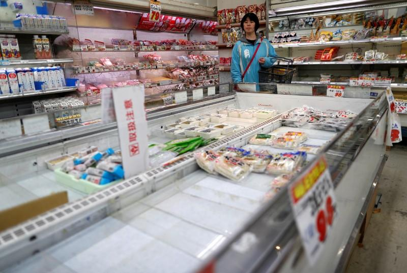 A shopper is seen next to empty shelves during an outbreak of the coronavirus disease (COVID-19), at a supermarket in Tokyo