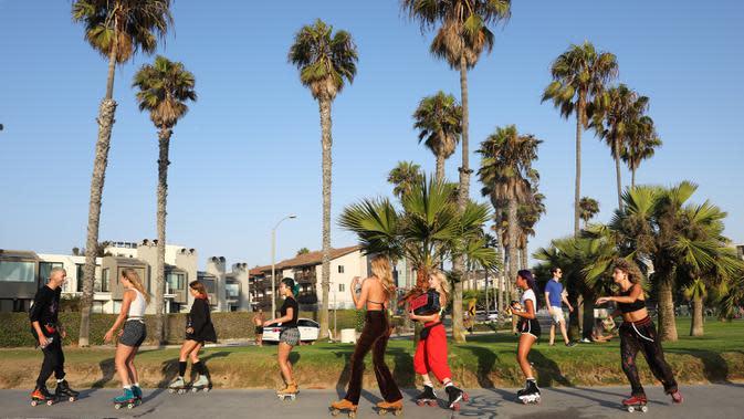 Orang-orang bermain sepatu roda di sepanjang Venice Beach di Venice, California, Kamis (3/9/2020). Permintaan sepatu roda di Amerika Serikat mengalami peningkatan tajam untuk mencari aktivitas di luar ruangan di tengah pembatasan sosial akibat corona Covid-19. (Mario Tama/Getty Images/AFP)