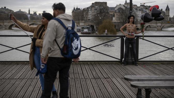 Pasangan berselfie dengan latar anggota gerakan feminis Femen yang dirantai selama aksi untuk mengecam kekerasan terhadap perempuan pada hari Valentine di pont des Arts, Paris (14/2/2020). (AFP Photo/Lionel Bonaventure)