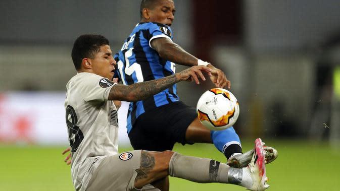 Bek Inter Milan, Ashley Young, berebut bola dengan pemain Shakhtar Donetsk, Dodo, pada laga semifinal Liga Europa di Merkur Spiel-Arena, Selasa (18/8/2020). Inter Milan menang dengan skor 5-0. (Lars Baron/Pool via AP)