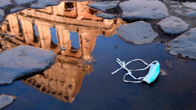 Refleksi bangunan Colosseum terlihat pada genangan air dengan masker di dekatnya, Roma, Italia, 8 Maret 2020. Hingga Kamis (12/3/2020) pagi, jumlah kasus virus corona COVID-19 di Italia sebanyak 12.462 orang terinfeksi, 827 meninggal, dan 1.045 sembuh. (Alfredo Falcone/LaPresse via AP)