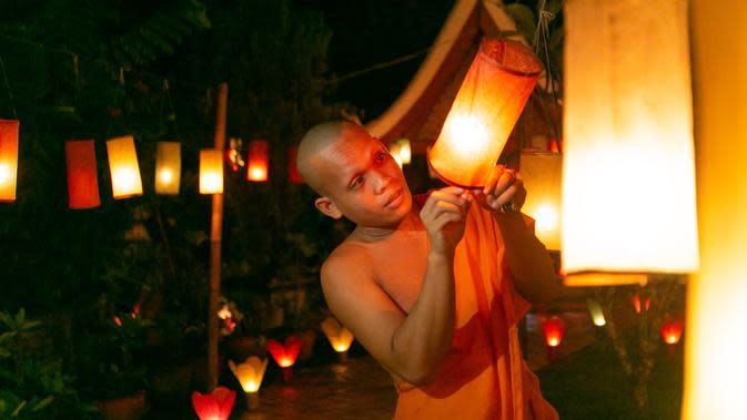 Biarawan menyalakan lentera di Luang Prabang, Laos, 3 Oktober 2020. Dalam Festival Boun Lai Heua Fai, warga melarung perahu naga dari batang pohon pisang yang membawa bunga, dupa, dan lilin menyusuri Sungai Mekong untuk membuang nasib buruk dan mengalirkan keberuntungan. (Xinhua/Kaikeo Saiyasane)