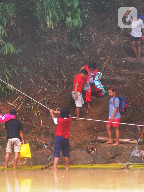 Warga bersiap menaiki rakit untuk menyeberangi Sungai Cikaniki di Rumpin, Bogor, Rabu (15/1/2020). Akibat banjir bandang merobohkan jembatan yang menghubungkan Desa Tonjong Rumpin dan Desa Kantalarang Leuwiliang, warga terpaksa memanfaatkan perahu rakit untuk melintas. (merdeka.com/Arie Basuki)