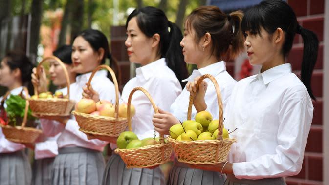 Para staf memamerkan produk-produk pertanian lokal pada pembukaan acara perayaan untuk menandai festival panen petani China di Distrik Pinggu, Beijing, ibu kota China, pada 24 September 2020. (Xinhua/Ren Chao)