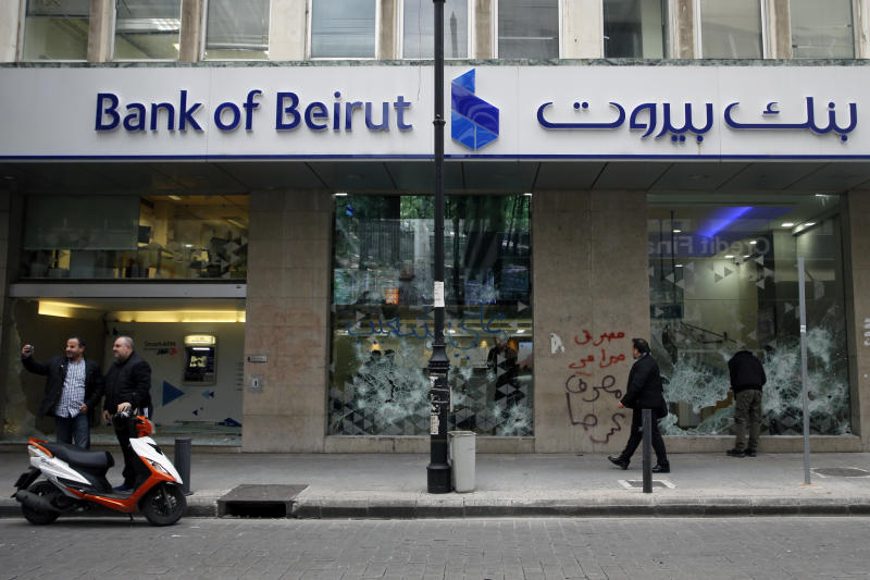 FILE - In this Jan. 15, 2020 file photo, people look at the broken facade of Bank of Beirut that was smashed by anti-government protesters in Beirut, Lebanon. Fitch Ratings said Tuesday, Feb. 18, 2020, that Lebanon's financial position points to a likely restructuring of the country's massive debt and financial sector as the Arab nation passes though its worst financial and economic crisis in decades. Fitch Ratings' report comes as Lebanese officials are debating whether to pay back $1.2 billion worth of Eurobonds that will mature on March 9. (AP Photo/Bilal Hussein, File)