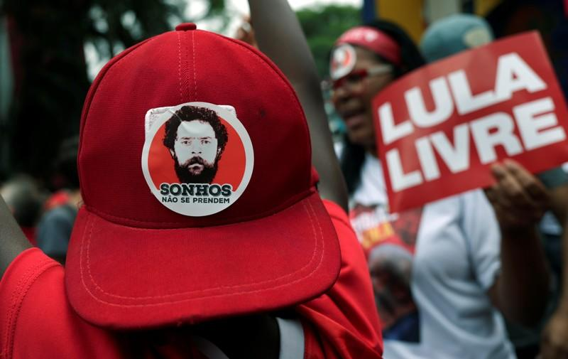 """A person wears a cap with sticker reading """"Dreams don't come true"""" as supporters of former Brazilian President Luiz Inacio Lula da Silva wait for his arrival after he was released from prison, in Sao Bernardo do Campo"""