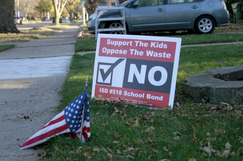 In this Oct. 31, 2019 photo, a yard sign opposing a school funding ballot measure is seen in Worthington, Minn. Voters in this southwestern Minnesota town will weigh nearly $34 million in new borrowing to expand schools filled to overflowing in recent years by an influx of immigrants, on, Tuesday, Nov. 5, 2019. (AP Photo/Stephen Groves)