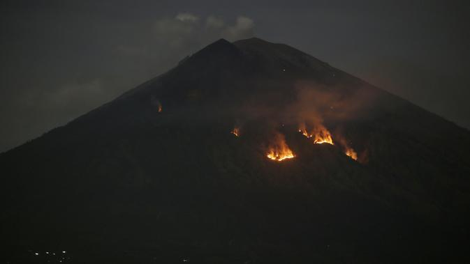 Api membakar hutan lereng Gunung Agung setelah terjadinya lontaran batu pijar dari kawah terlihat dari Karangasem, Bali, Selasa (3/7). Lontaran lava pijar pun teramati keluar kawah dengan jarak mencapai 2 ribu meter. (AP/Firdia Lisnawati)
