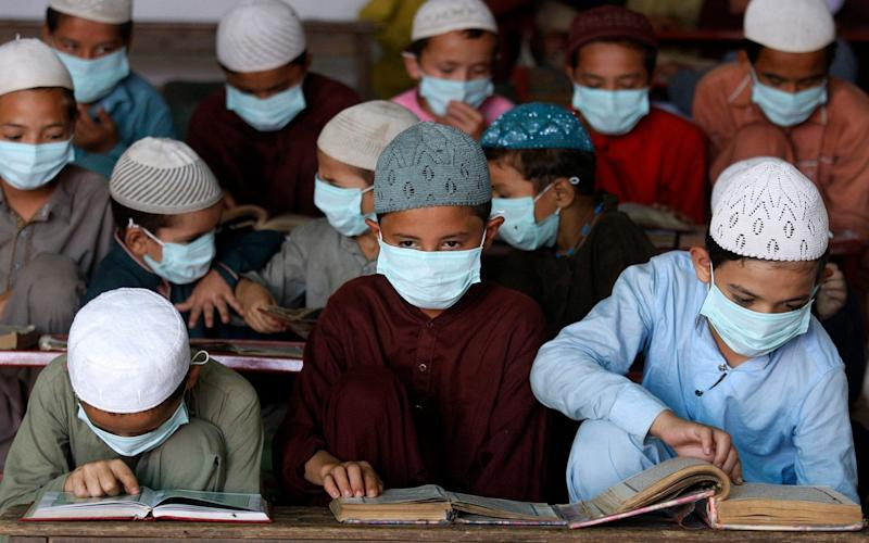 Children wearing face masks to prevent the spread of coronavirus read the Quran at a religious school in a mosque, in Karachi, Pakistan - AP