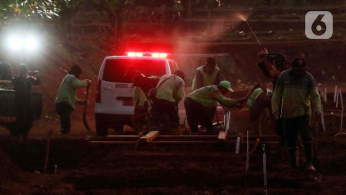 Petugas melakukan proses pemakaman jenazah pasien terinfeksi COVID-19 di TPU Pondok Ranggon, Jakarta, Selasa (8/9/2020). Hingga Selasa (8/9) jumlah kasus Covid-19 di Indonesia 200.035 orang, pasien dirawat 48.847, meninggal 8.230 dan sembuh 142.958. (Liputan6.com/Helmi Fithriansyah)