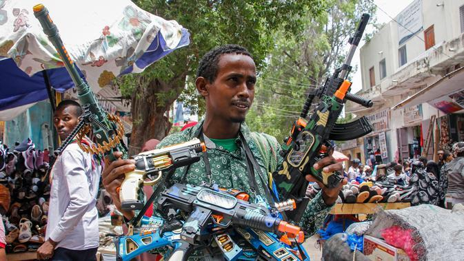 Seorang pedagang menjual senjata mainan jelang Hari Raya Idul Fitri yang menandai akhir bulan puasa Ramadhan, di Mogadishu, Somalia, (19/5/2020). (AP Photo/Farah Abdi Warsameh)