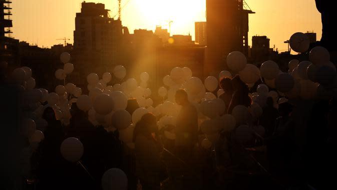 Orang-orang bersiap menerbangkan balon dalam upacara untuk memperingati peristiwa ledakan pelabuhan 4 Agustus di Beirut, Lebanon, 4 Oktober 2020. Dua ledakan yang mengguncang Pelabuhan Beirut menghancurkan sebagian kota dan menewaskan sekitar 190 orang. (Xinhua/Bilal Jawich)