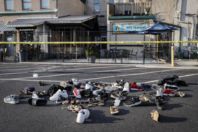 "FILE - In this Sunday, Aug. 4, 2019, file photo, shoes are piled outside the scene of a mass shooting in Dayton, Ohio. In a period of around 10 weeks in 2019, Dayton dealt with a Ku Klux Klan rally, a string of devastating tornadoes, and a mass shooting that killed nine people. Mayor Nan Whaley's end-of-the-year reflections include searing memories of the natural disaster and attack as she looks ahead to a year dedicated to ""healing and transformation."" (AP Photo/John Minchillo, File)"