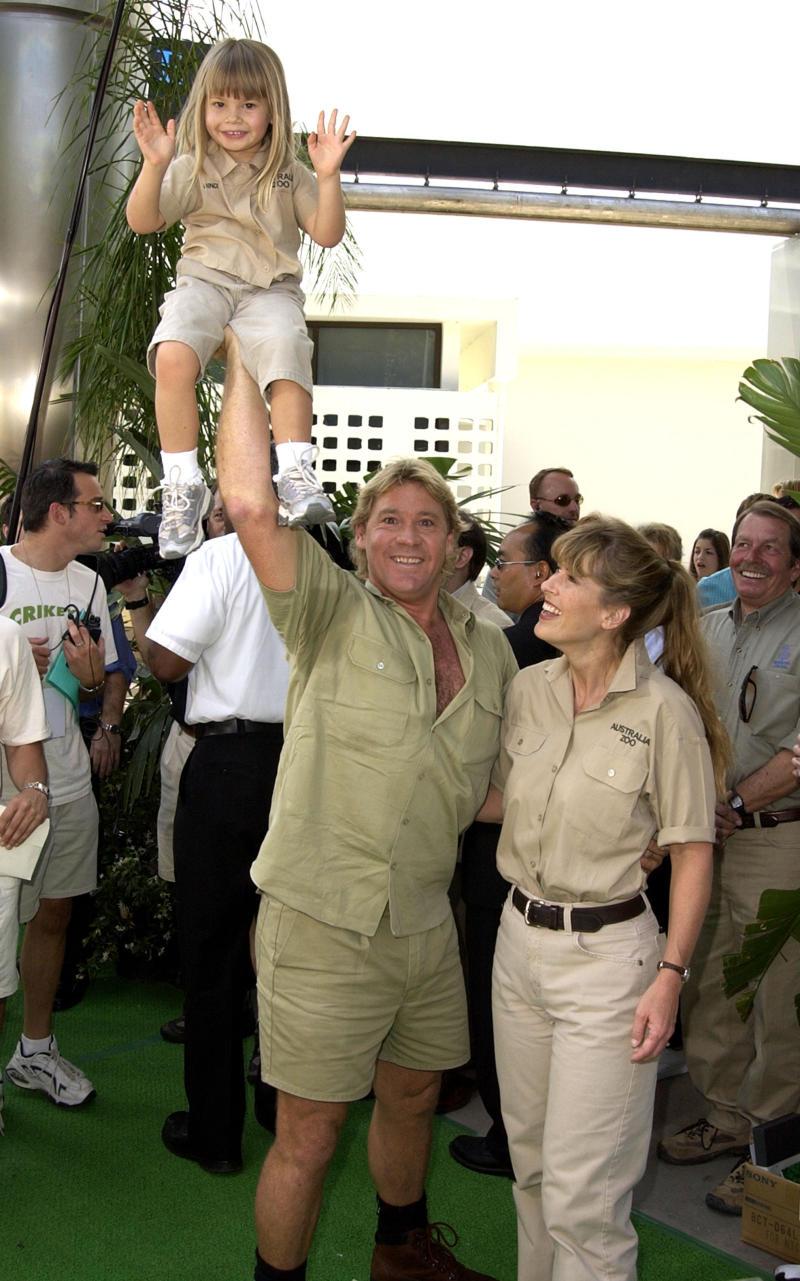 Bindi Irwin is held up by her dad, Steve Irwin as her mum, Terri Irwin, laughs.