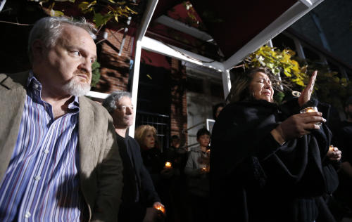 Chef Art Smith, left, watches Chef Priscila Satkoff fight back tears as she pays tribute to Chicago Chef Charlie Trotter during a candlelight memorial for Trotter outside his former restaurant Tuesday, Nov. 5, 2013, in Chicago. Trotter, 54, died Tuesday, a year after closing his namesake Chicago restaurant that was credited with putting his city at the vanguard of the food world and training dozens of the nation's top chefs, including Grant Achatz and Graham Elliot. (AP Photo/Charles Rex Arbogast)