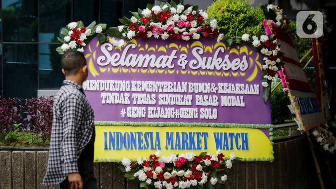 Seorang pria melintas di depan karangan bunga dukungan di halaman Kementerian BUMN Jakarta, Kamis (16/1/2020). Kantor Menteri BUMN Erick Thohir kembali mendapat kiriman bunga berupa dukungan untuk menyelesaikan masalah PT Asuransi Jiwasraya (Persero). (Liputan6.com/Faizal Fanani)