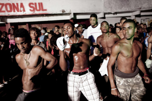 "In this Feb. 3, 2012 photo, people dance at a funk ""baile"" in the Cantagalo slum in Rio de Janeiro, Brazil. In the last five years, the genre has expanded its reach and enjoyed more social acceptance, with the help of an association of funk artists and supporters, Apafunk, and the backing of liberal legislators. Its market potential has become hard to ignore: A recent survey by the Brazilian think tank the Getulio Vargas Foundation found funk disc jockeys, MCs and others generate about $720 million a month in revenue. (AP Photo/Felipe Dana)"