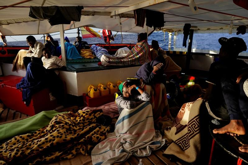Migrants rest on board of NGO Proactiva Open Arms rescue boat in central Mediterranean Sea