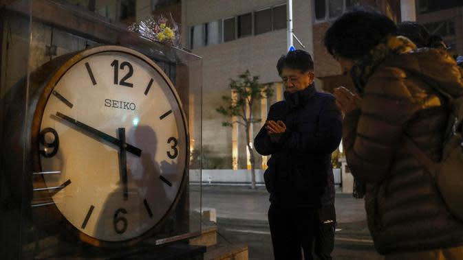 Orang-orang berdoa di samping jam yang menunjukkan waktu dari gempa kuat pada 17 Januari 1995, di Nishinomiya, Jepang (17/1/2020). Jepang menandai peringatan 25 tahun gempa Kobe yang menewaskan lebih banyak lebih dari enam ribu orang dan menghancurkan sebagian besar kota. (Kyodo News via AP)