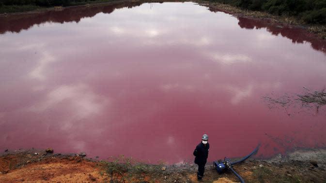 Seorang pekerja berdiri dekat pompa saat mengambil air untuk pengujian dari Cerro Lagoon yang berwarna merah muda dan berbau busuk di Limpio, Paraguay, 2 September 2020. Pencemaran air terjadi akibat limbah yang diduga berasal dari perusahaan penyamakan kulit Waltrading SA. (AP Photo/Jorge Saenz)