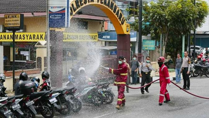 Petugas Pemadam Kebakaran Kota Pekanbaru menyemprotkan cairan disinfektan untuk mencegah penyebaran virus corona. (Liputan6.com/Hms Pemko Pekanbaru/M Syukur)