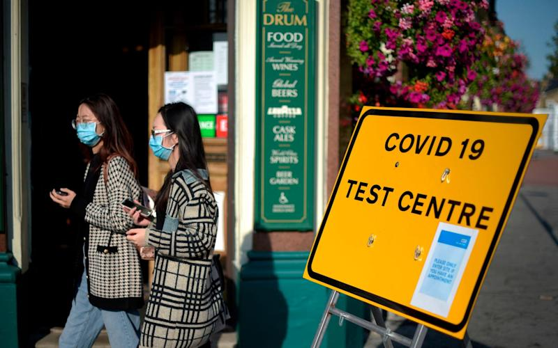 Pedestrians walk past a sign for a Covid-19 test centre this afternoon in Leyton, east London - Getty