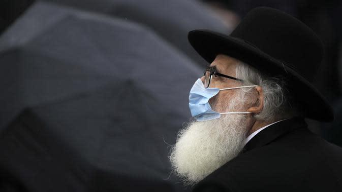 Rabbi Rafael Schaffer mengenakan masker untuk perlindungan terhadap infeksi COVID-19 saat Hari Peringatan Holocaust Nasional di Bucharest, Rumania, Jumat (9/10/2020). Pada tahun 1941, orang Yahudi dan Roma dideportasi dari Rumania saat negara itu diperintah rezim pro Nazi. (AP Photo/Vadim Ghirda)