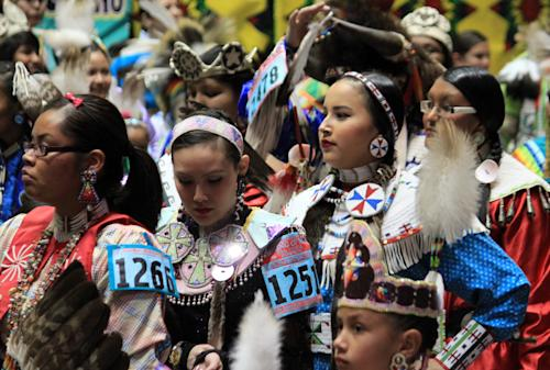 Native American and indigenous dancers file into University of New Mexico Arena during the grand entry at the 30th annual Gathering of Nations in Albuquerque, N.M., on Friday, April 26, 2013. The powwow draws hundreds of competitive dancers and tens of thousands of spectators each year. (AP Photo/Susan Montoya Bryan)