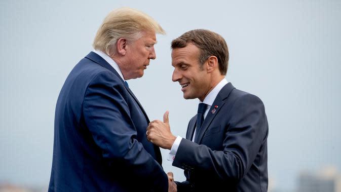 Presiden Prancis Emmanuel Macron (kanan) menyambut kedatangan Presiden AS Donald Trump (kiri) di KTT G7, Biarritz, Prancis, Sabtu (24/8/2019). G7 adalah sebuah grup yang terdiri dari Kanada, Prancis, Jerman, Italia, Jepang, Britania Raya, dan Amerika Serikat. (AP Photo/Andrew Harnik)