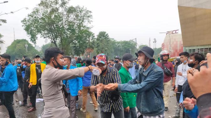 Salah satu polisi membantu para demonstran di Palembang, dengan memberikan air mineral (Liputan6.com / Nefri Inge)