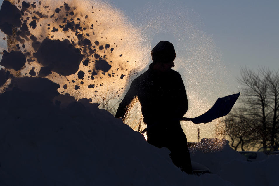 Peter Bloom digs his car out of a parking lot at sunrise, Sunday, Feb. 10, 2013, in Portland, Maine. Residents are digging out after a blizzard dumped a record 31.9 inches of snow on the city.  (AP Photo/Robert F. Bukaty)