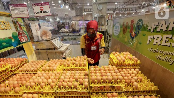 Karyawan memilih telur yang dibatasi dengan plastik di supermarket AEON Mall BSD City, Tangerang, Rabu (3/6/2020). Pembatasan tersebut dilakukan untuk memberikan jarak sosial dalam interaksi antara karyawan dan konsumen selama pandemi Covid-19. (Liputan6.com/Fery Pradolo)