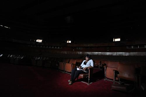 A worker sits in the abandoned bowl theater of Nigeria's National Theatre in Lagos, Nigeria, on Thursday, April 4, 2013. Nigeria's iconic National Theatre, long in disrepair, is now at the center of a massive redevelopment plan that could be worth millions of dollars. Nigeria's federal government has plans to use money leasing the swampy land in Lagos around the theater to private investors so they can build a mall, a five-star hotel and other amenities. However, some have doubts that the project will actually raise money for the theater. Meanwhile, the plans have already likely encouraged local officials to demolish the homes of slum dwellers living around the theater. (AP Photo/Jon Gambrell)