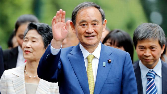 Perdana Menteri Jepang, Yoshihide Suga melambaikan tangan saat berjalan setibanya di Istana Kepresidenan, di Hanoi, Vietnam, Senin (19/10/2020). Yoshihide Suga melakukan kunjungan resmi ke Vietnam hingga 20 Oktober 2020. (AP Photo/Minh Hoang, Pool)
