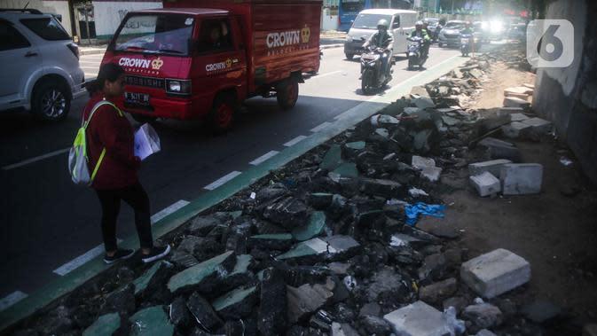 Pejalan kaki melintas di samping jalur sepeda yang di bongkar di kawasan Cikini, Jakarta, Selasa (19/11/2019). Jalur sepeda berumur 2 bulan tersebut dibongkar akibat proyek pelebaran trotoar. (Liputan6.com/Faizal Fanani)