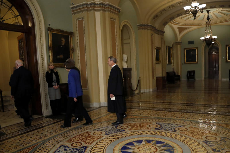 Chief Justice of the United States John Roberts, right, walks to the Senate chamber at the Capitol in Washington, Thursday, Jan. 16, 2020. (AP Photo/Julio Cortez)