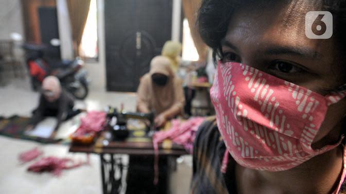 Seseorang memakai masker kain buatan ibu-ibu PKK di Desa Bojongkulur, Gunung Putri, Bogor, Jawa Barat, Kamis (9/4/2020). Saat pelaksanaan isolasi mandiri akibat COVID-19, ibu-ibu PKK ini membuat masker untuk dibagikan secara gratis kepada warga sekitar. (merdeka.com/Arie Basuki)